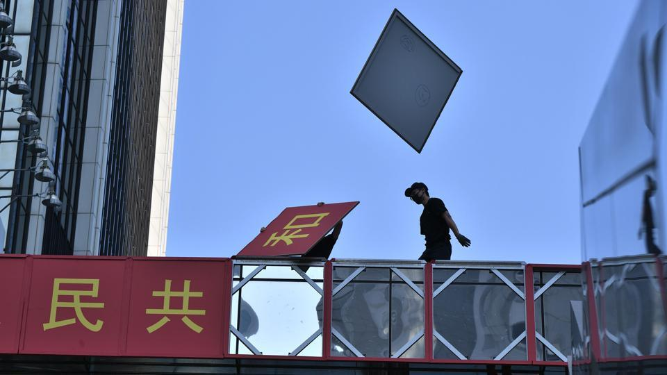 A protester removes the signage celebrating the 70th anniversary of communist China's founding from a footbridge during a rally in the Admiralty district of Hong Kong. Hong Kong police shot a pro-democracy protester yesterday as the city was lashed by its worst unrest of the year. This was the first such incident in nearly four months of increasingly violent protests and threatened to strip the spotlight from China's carefully choreographed birthday party. (Anthony Wallace / AFP)
