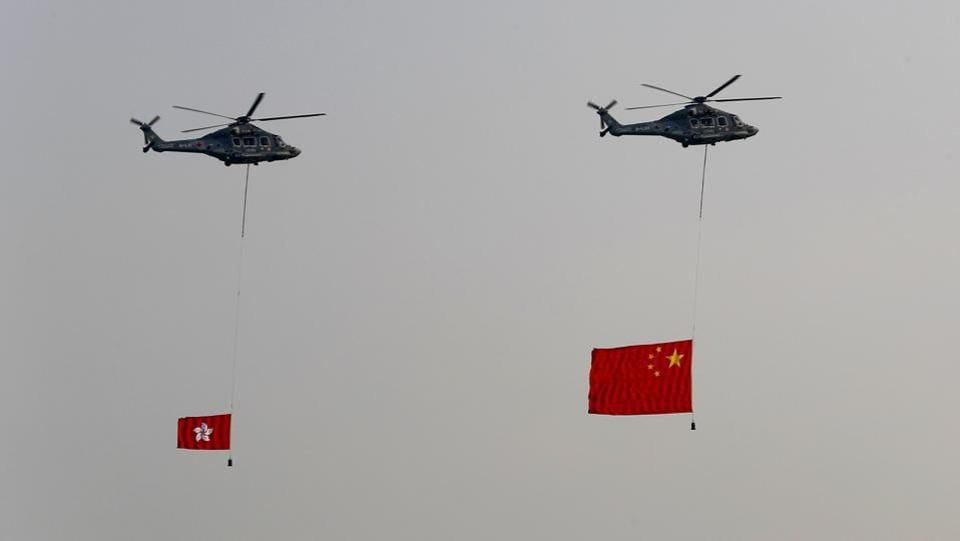 Helicopters fly over with displaying the flag of China, right, and the flag of Hong Kong, in Hong Kong while the celebration of the People's Republic's 70th anniversary is taking place in Beijing. Police warned of the potential for protesters to engage in violence