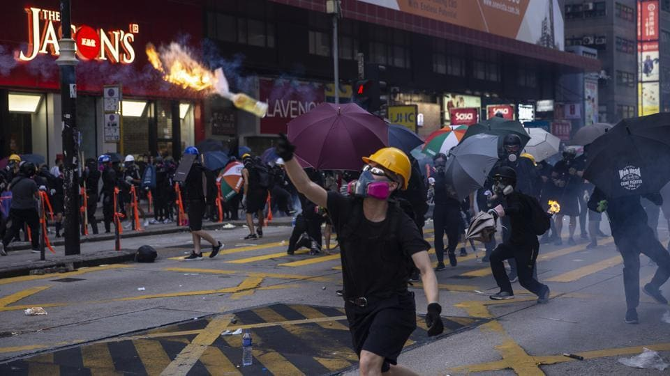 Demonstrators throw petrol bombs towards riot police during a protest in the Mong Kok district of Hong Kong.  Hospital authorities said more than 70 people were admitted on Tuesday. Police made some 160 arrests throughout the day. On Wednesday, 96 protesters arrested during clashes with police on Sunday appeared in court charged with rioting, according to court documents. Their ages ranged from 14 to 39. (Chan Long Hei / Bloomberg)