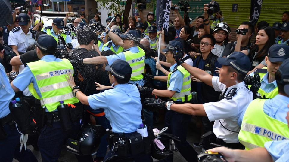 Hong Kong police use pepper-spray as a fight breaks out between pro-democracy protesters who were carrying a mock coffin and another man early morning in the Wanchai district in Hong Kong. The unrest in Hong Kong illustrated the challenges faced by China, which is also contending with US trade war negotiations. (Nicolas Asfouri / AFP)