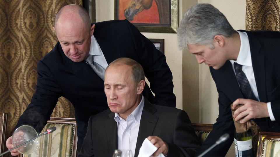 FILE - In this Friday, Nov. 11, 2011, file photo, businessman Yevgeny Prigozhin, left, serves food to Russian Prime Minister Vladimir Putin, center, during dinner at Prigozhin's restaurant outside Moscow, Russia. The U.S. sought to punish Russia on Monday, Sept. 30, 2019, for interfering with the November 2018 election by placing the yacht and private planes of a Russian financier, Yevgeny Prigozhin, on an international sanctions list along with employees of the Internet Research Agency that he has funded to spread false information on social media.