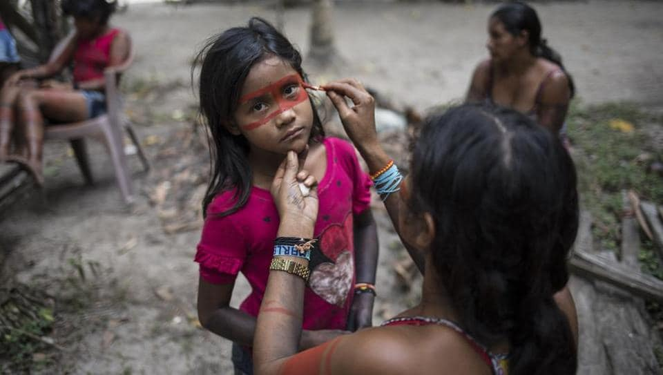 A child stands still as a woman paints a red mask around her eyes in preparation for a gathering of tribes in the Alto Rio Guama Indigenous Reserve by the Tembe tribes in the village Tekohaw, Para state, Brazil. The Tembe indigenous people of Brazil's Amazon rainforest for generations have painted their bodies for rites of passage, weddings and to symbolize that they're ready for war. (Rodrigo Abd / AP)