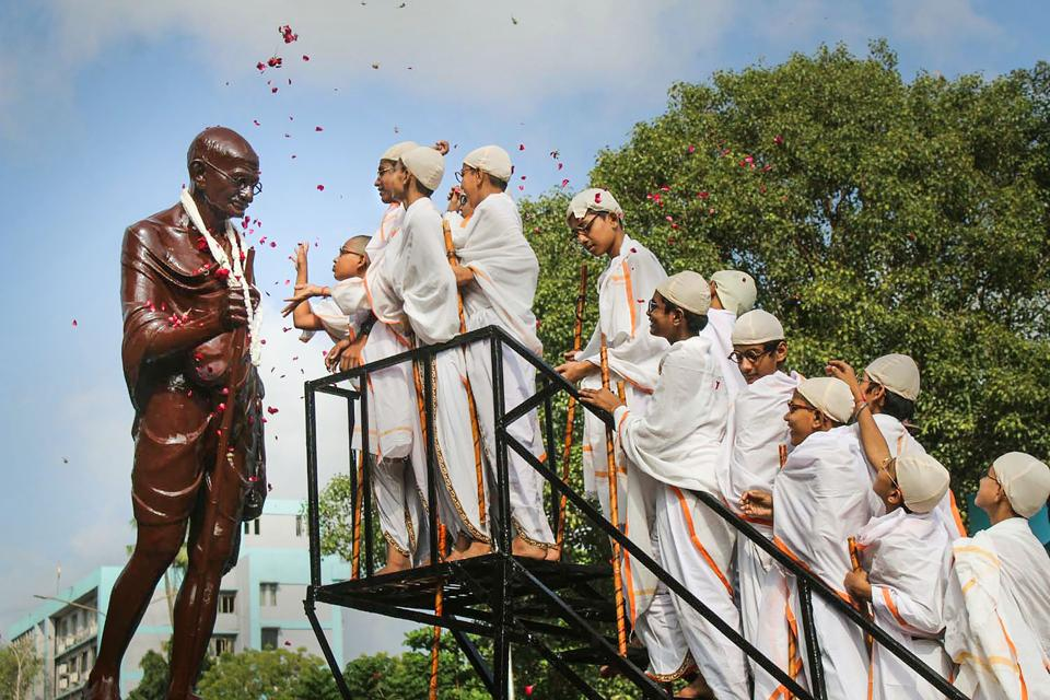 Students offer tribute to Mahatma Gandhi on his 150th birth anniversary, in Surat, on Wednesday.