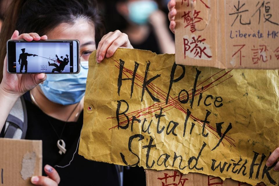People hold up signs and a mobile phone as they gather at West Kowloon Law Courts Building to show their support to 96 anti-government protesters who were arrested days ago in Hong Kong, China, October 2, 2019