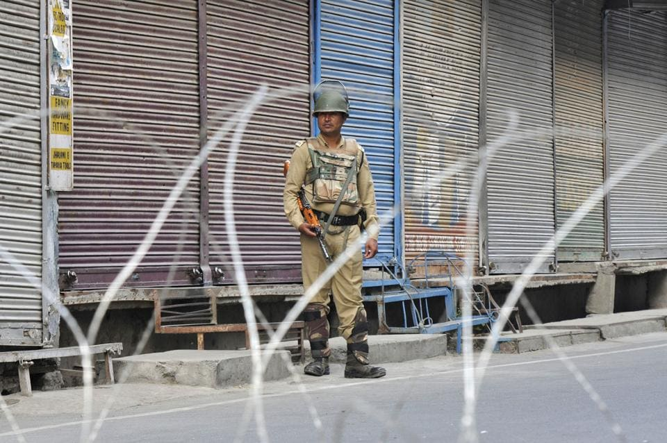 A paramilitary soldier stands guard near barbed wires during restrictions, at Lal Chowk, in Srinagar, Jammu and Kashmir, India, on Friday, September 27, 2019.