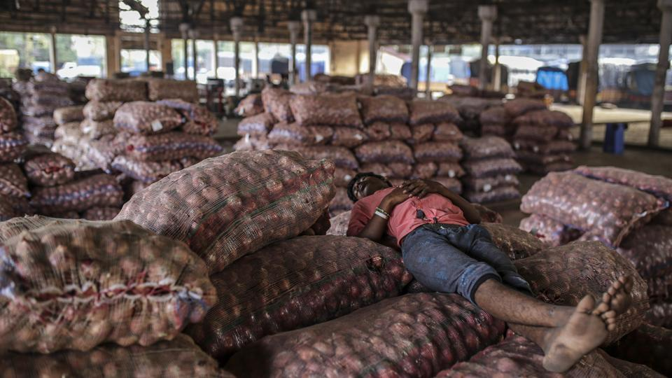 A worker sleeps on sacks of onions at the Vashi Agricultural Produce Market Committee (APMC) wholesale market in Mumbai, Maharashtra. Onions in India are once more at the epicentre of a major controversy, pitting government officials who want lower prices against farmers that need extra income. (Dhiraj Singh / Bloomberg)