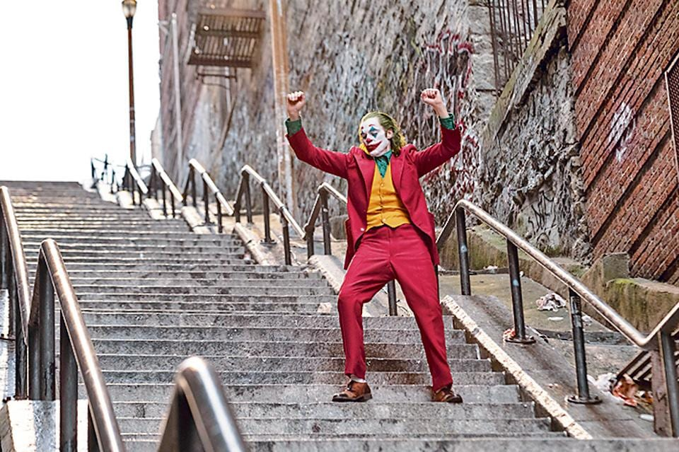 In the movie, lead actor Joaquin Phoenix dances as he goes down the steps, wearing a bright red suit and clown makeup.