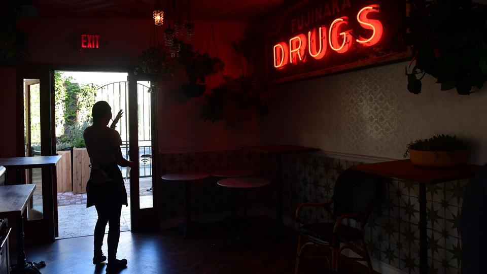 "A waitress is silhouetted through a doorway at the cafe.  ""We're enjoying the day, the music's good, the weather's good and we're in California. Life can't get better,"" Kirschner added. (Frederic J. Brown / AFP)"