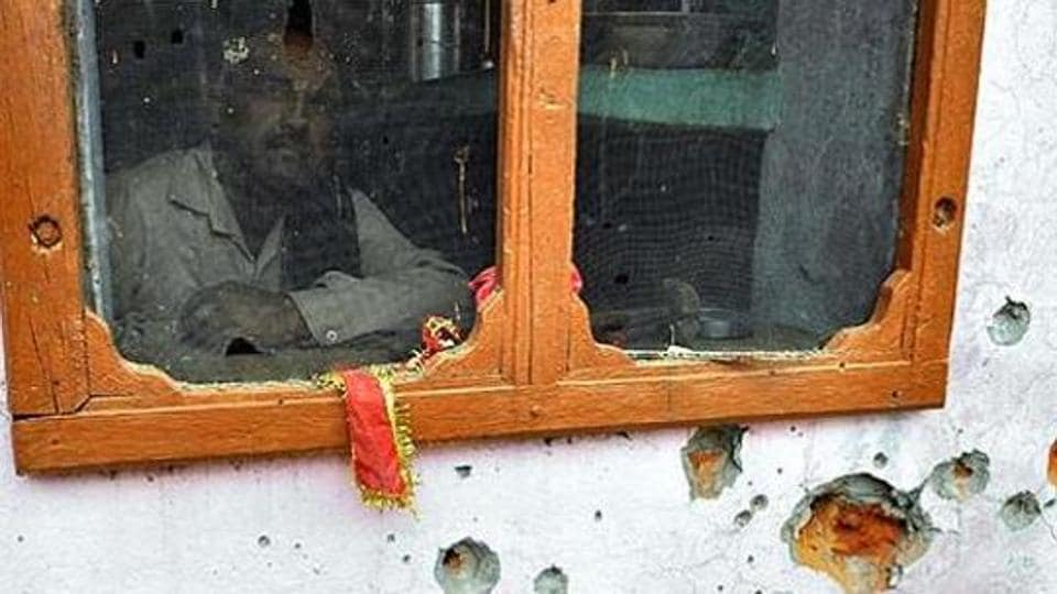 A villager looks through the window of a house whose walls were damaged in the Pakistan firing at Chilyari village, Samba in Jammu.