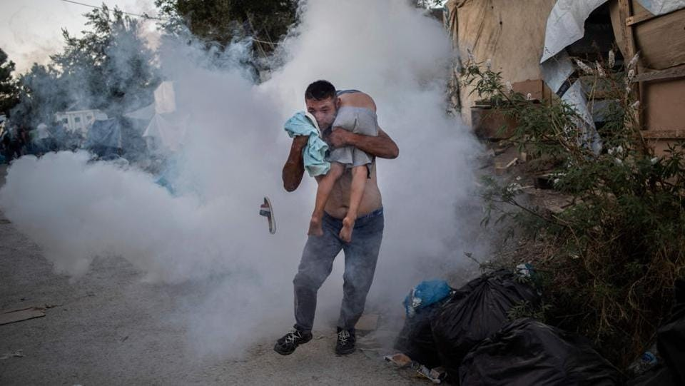 A man holds a boy during clashes with police outside the refugee camp of Moria on the Greek island of Lesbos. At least one migrant died on September 29, 2019, after a fire broke out in Moria, the over-crowded refugee camp on the Greek island of Lesbos, Greece's Health Ministry said. (Angelos Tzortzinis / AFP)