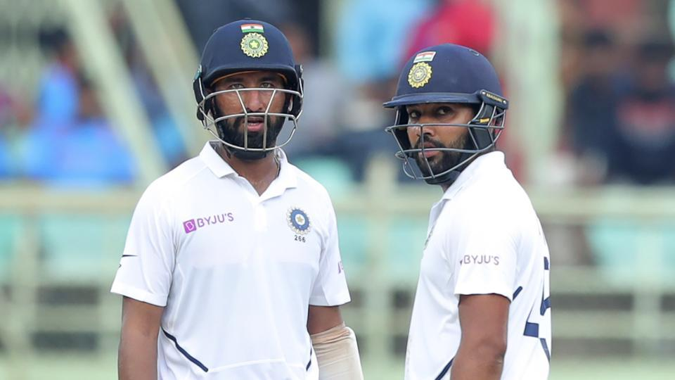 India's Rohit Sharma, right, and Cheteshwar Pujara stand in the field during the fourth day of the first Test.