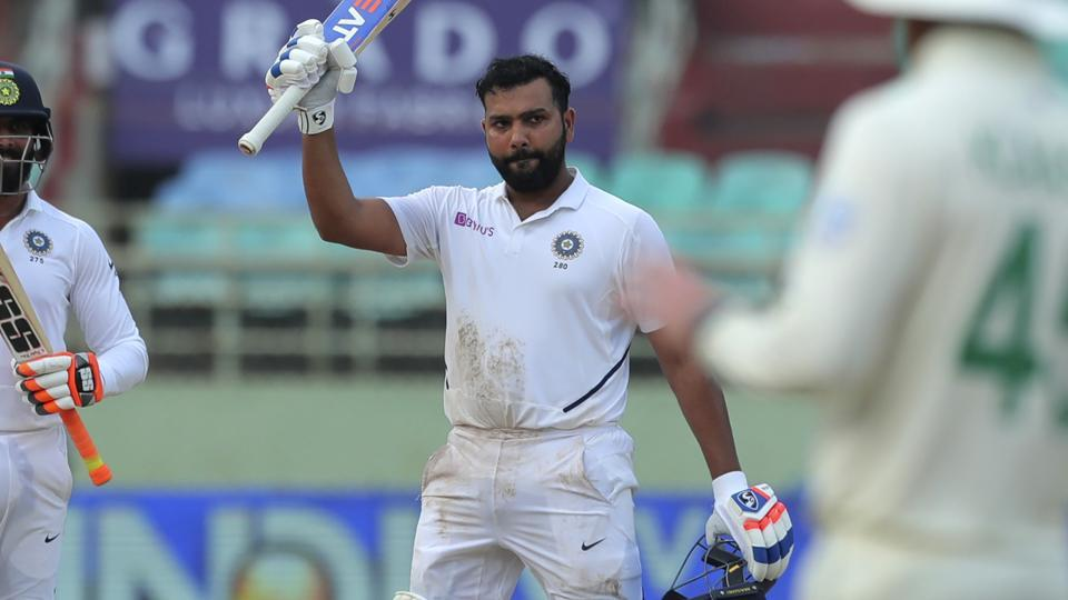 India's Rohit Sharma raises his bat after scoring a century during the first test match against South Africa in Visakhapatnam.