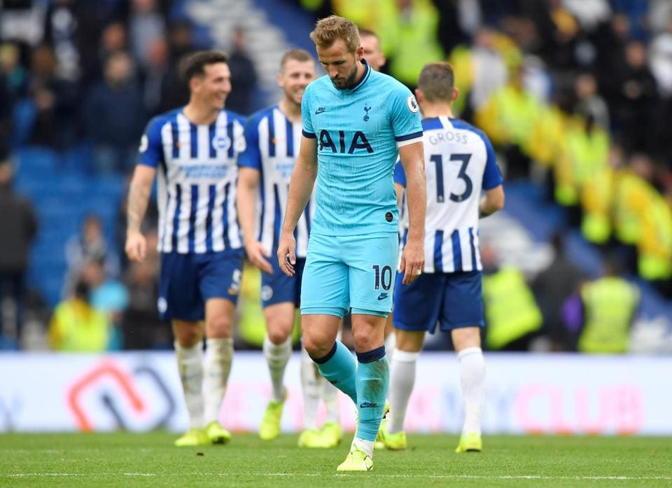 Tottenham Hotspur's Harry Kane looks dejected as Brighton and Hove Albion players celebrate at the end of the match.