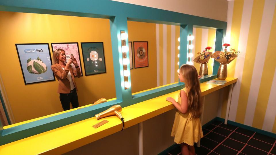 A girl poses for a photo during a visit to the Instagram museum