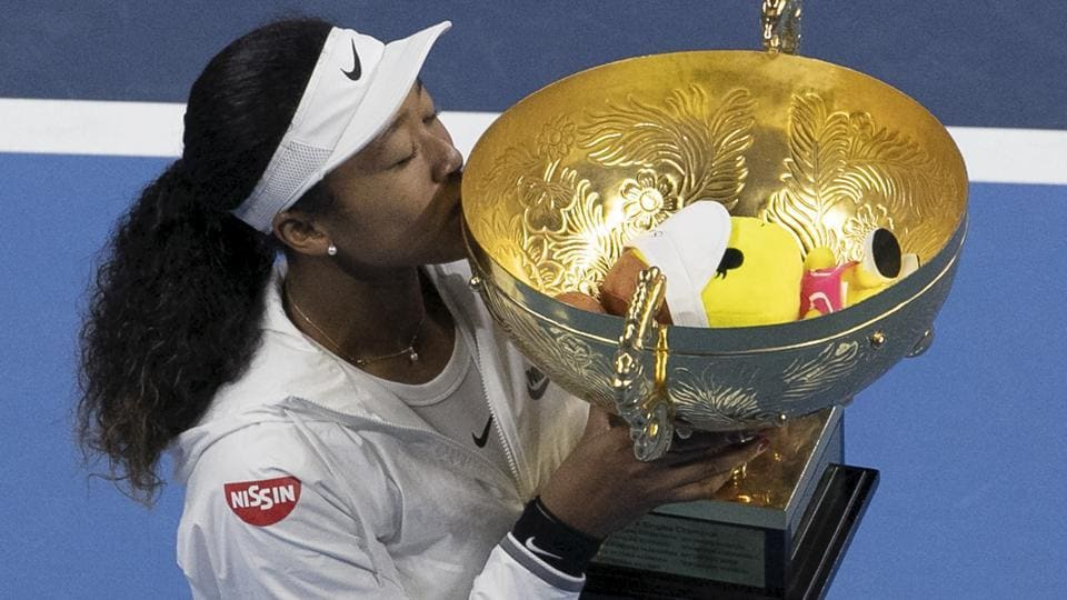 Naomi Osaka kisses her winner's trophy after defeating Ashleigh Barty in the women's final at the China Open.