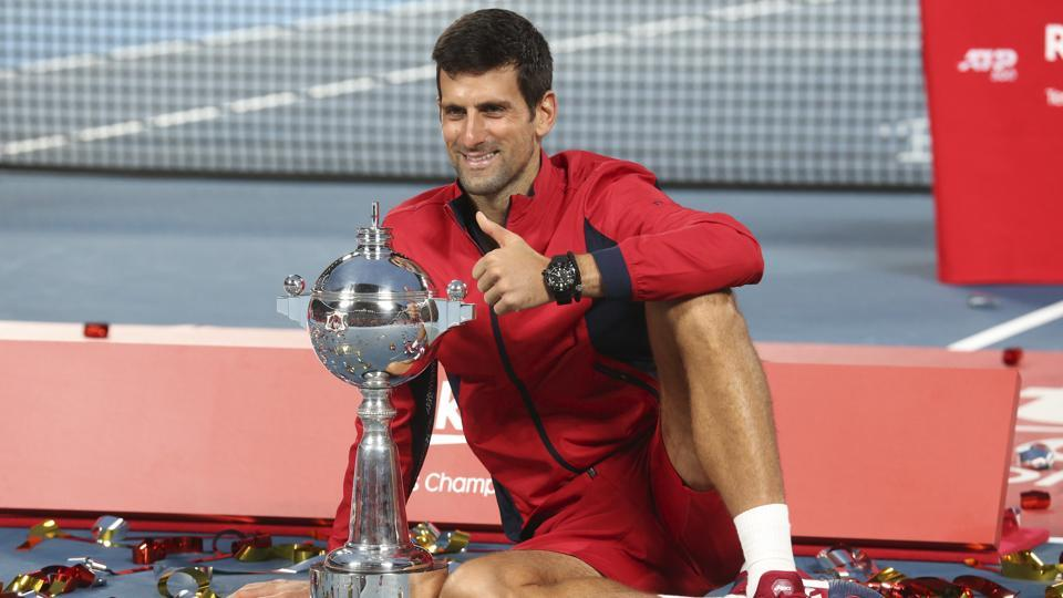 Novak Djokovic poses with his champion trophy during the award ceremony of the Japan Open.