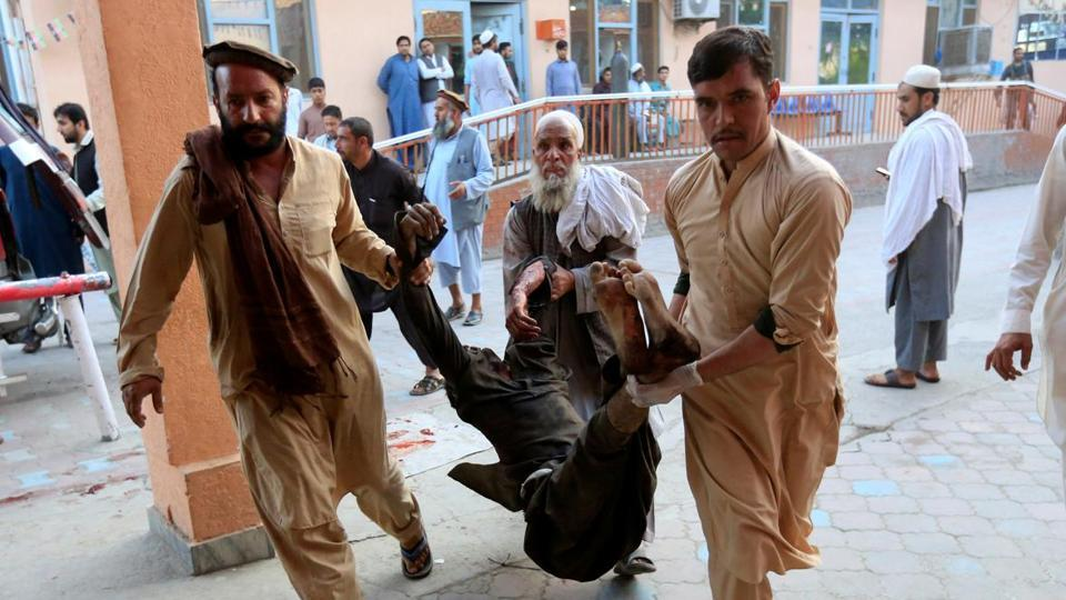Men carry an injured person to a hospital after a blast in Jalalabad, Afghanistan