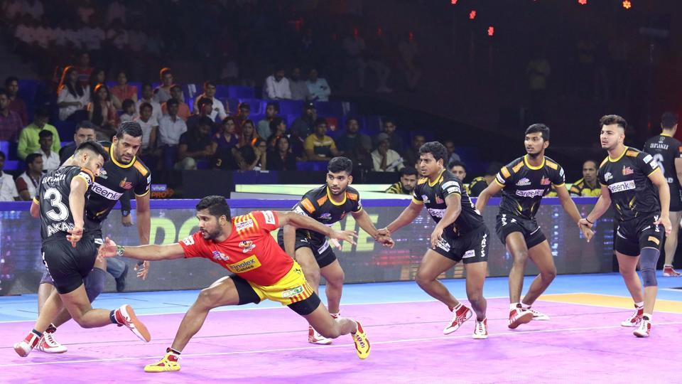 Gujarat Fortunegiants try to stop a Telugu Titans raider.