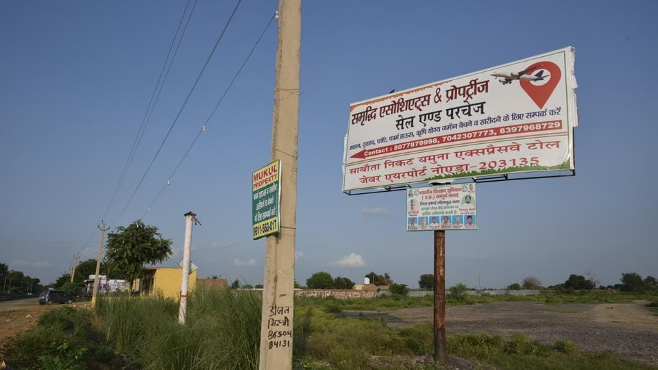 A sale and purchase for land signboard is seen in Jewar village. The Uttar Pradesh government has acquired land from farmers for the upcoming Noida International Airport in Jewar village, completing 75 per cent of required acquisition for the first phase of the project. The first phase of the airport would be spread over 1,334 hectare and is expected to be completed by 2023, according to officials.  (Biplov Bhuyan/HT Photo)