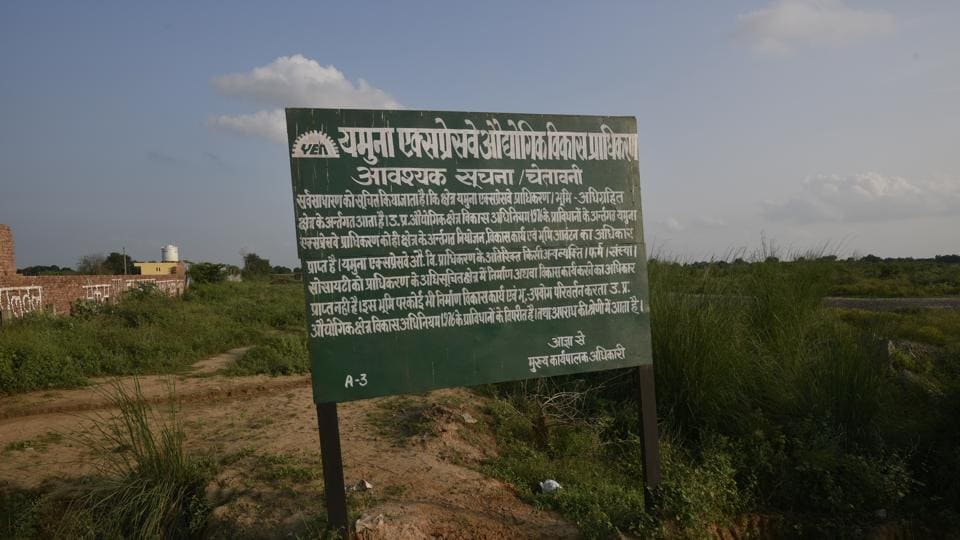The agricultural fields in the village have the last standing crop, and boards put by Yamuna Expressway Industrial Development Authority (YEIDA) with a 'statutory warning' that the land has been acquired by the UP government for the Noida International Airport, Jewar.  (Biplov Bhuyan/HT Photo)