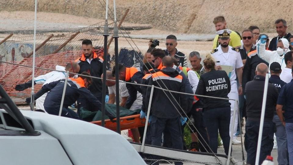 Rescue personnel carry a stretcher off a rescue vessel, after a ship carrying some 50 migrants began taking on water off the coast of Lampedusa, Italy October 7, 2019.