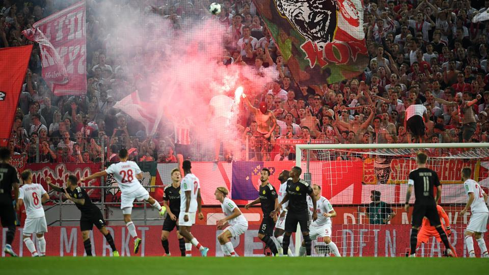 The 1. FC Koeln fans light a flare during the Bundesliga match between 1. FC Koeln and Borussia Dortmund at RheinEnergieStadion on August 23, 2019 in Cologne, Germany