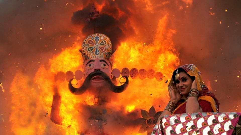 A lady dressed as Hindu goddess Sita puts her fingers in ears as an effigy of king Ravana goes up in flames during Dussehra festival in Jammu. (Nitin Kanotra / HT Photo)