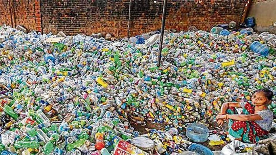 A woman sits among plastic bottles segregated for recycling.