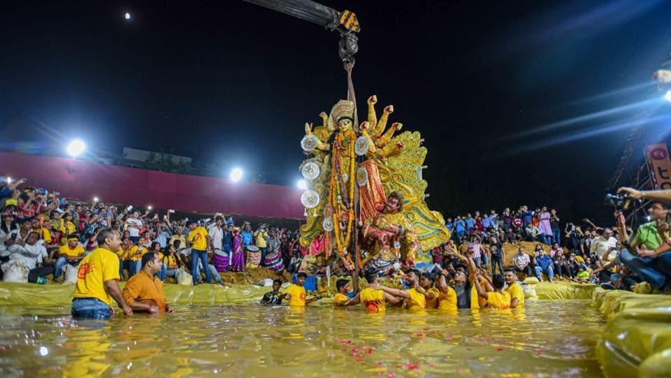 Devotees immerse an idol of goddess Durga into an artificial pond at CR Park. The idols of goddess Durga were for the first time immersed in an artificial pond instead of the Yamuna. The idol immersion protocol was followed by more than 500 Durga Puja committees in the city on Tuesday. Together, they gave up a ritual where idols were taken to the Yamuna as part of a procession and immersed there. (Amal KS / HT Photo)