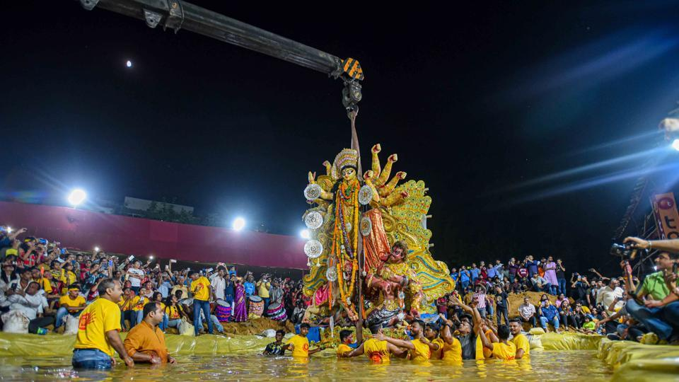Devotees immerse an idol of Goddess Durga in an artificial pond at CR Park, in New Delhi.  (Amal KS/Hindustan Times)