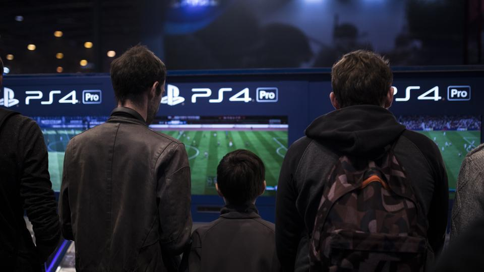 In this Nov. 3, 2017, photo, visitors play FIFA 18 video game on Playstation 4 Pro (PS4) at the Paris Games Week in Paris.