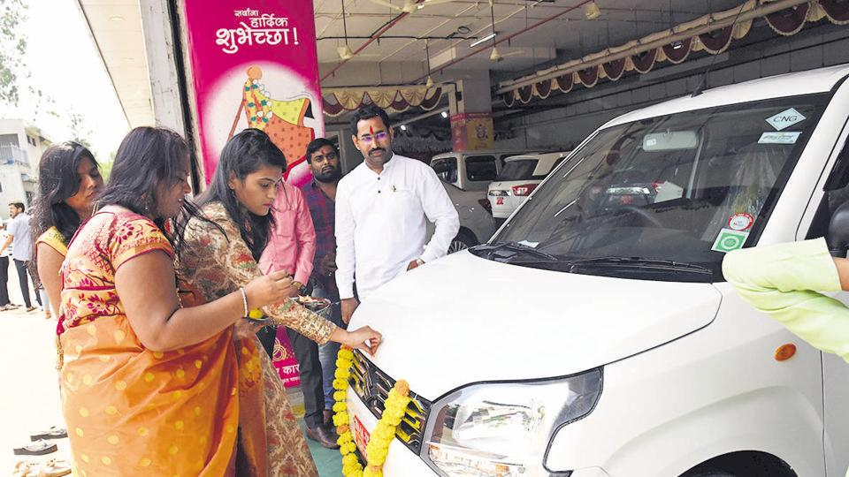 People purchase a vehicle on the occasion of Dussehra at a Maruti showroom in MIDC Bhosari in Pune, India, on Monday,October 07, 2019.