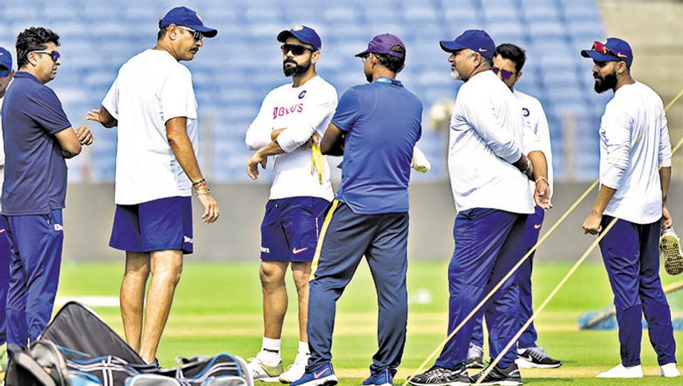 (2nd from left) Indian cricket team head coach Ravi Shastri and captain Virat Kohli interact with ground staff at MCAstadium in Pune on Wednesday.