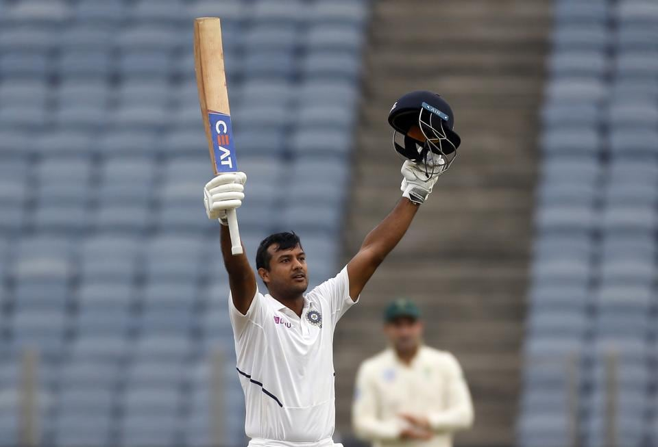 India's Mayank Agarwal raises his bat and helmet to celebrate scoring a century during the second cricket test match between India and South Africa in Pune. (AP)