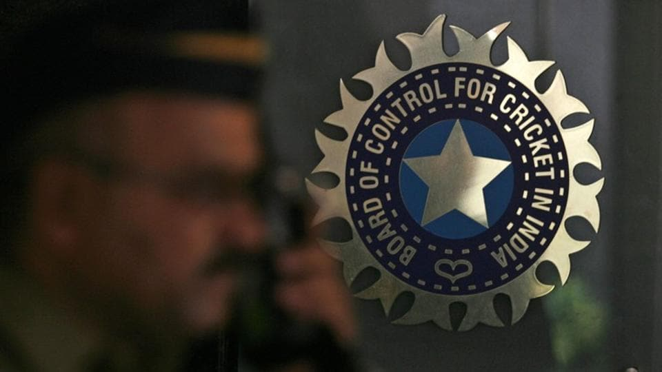 A policeman walks past a logo of the Board of Control for Cricket in India (BCCI)