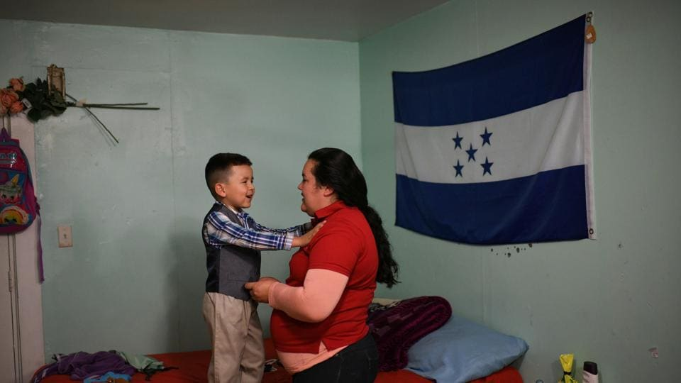 """Irma Rivera, an asylum-seeker from Honduras, prepares her son Jesus for church at their home in Fort Worth, Texas. Irma's husband, Jose, was murdered back home. Still grieving for her husband, she has struggled to adjust to American life. Every time something new happens, """"I want to tell him about it."""" She has arrived with straightforward expectations. """"I thought the children would go to school, and I'd work, and I'd get settled,"""" she said.  (Loren Elliott / REUTERS)"""