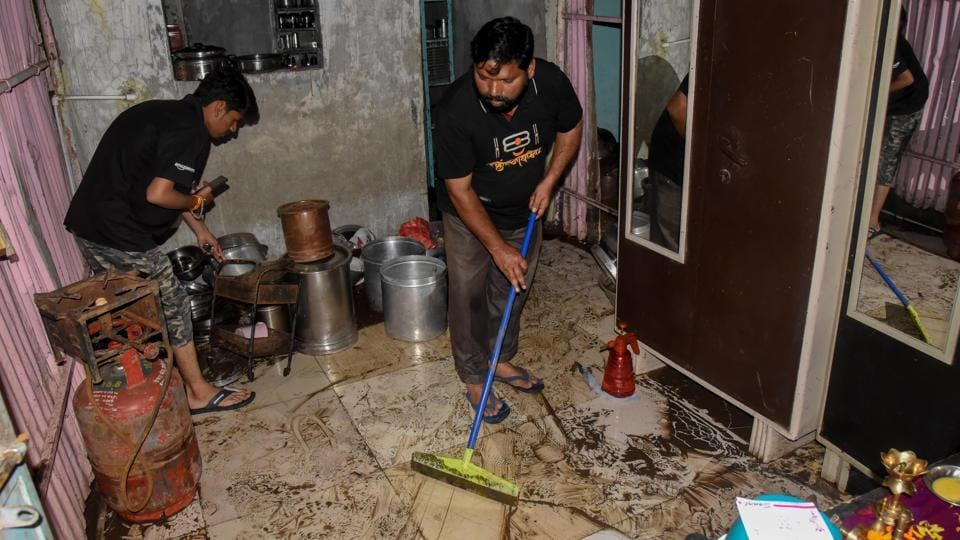 Residents of Tangewala colony clean their houses after waterlogging due to heavy rains on Wednesday.