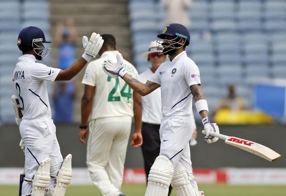 India's cricketer Virat Kohli, right, celebrates his hundred with Ajinkya Rahane during the second day of the second cricket test match between India and South Africa in Pune. (AP)