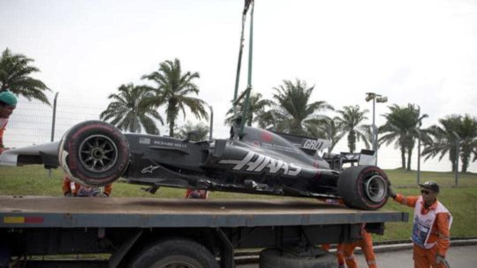 Track crew lifting Haas driver Romain Grosjean's car at the Malaysian Formula One Grand Prix.