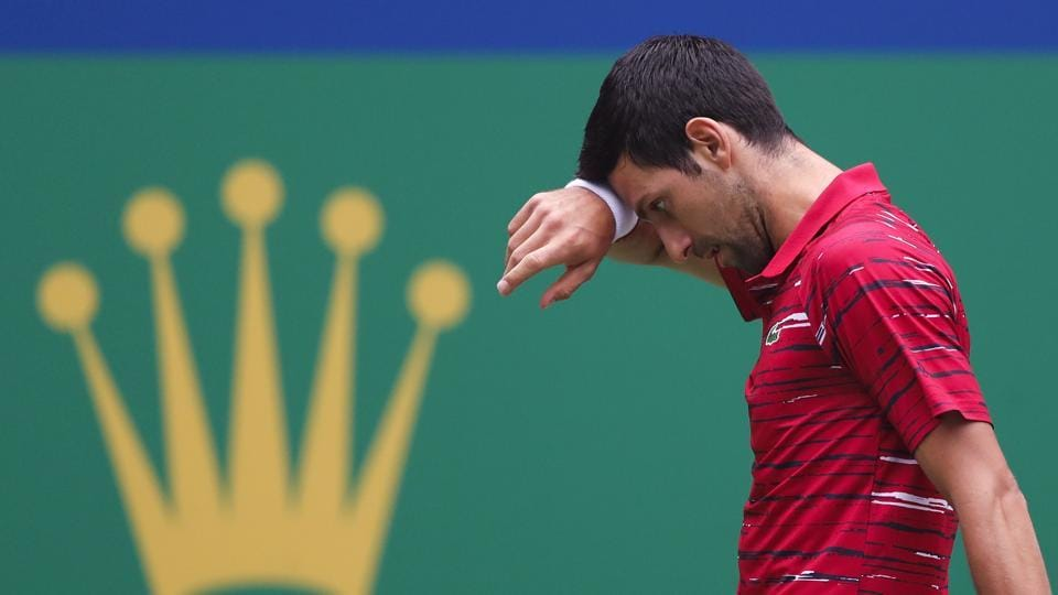 Novak Djokovic wipes his sweat as he plays against Stefanos Tsitsipas at the Shanghai Masters.
