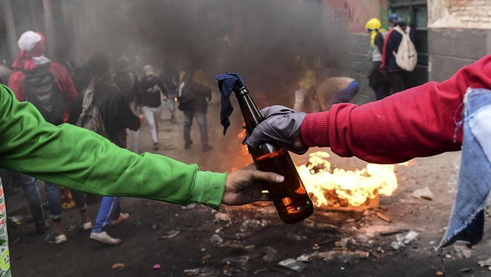 Demonstrators pass on a Molotov cocktail during clashes with riot police in Quito. Protests against fuel price hikes in Ecuador a week ago have escalated into violent clashes, leaving five protesters dead and leading the government to suspend two-thirds of its crude oil distribution. (Martin Bernetti / AFP)