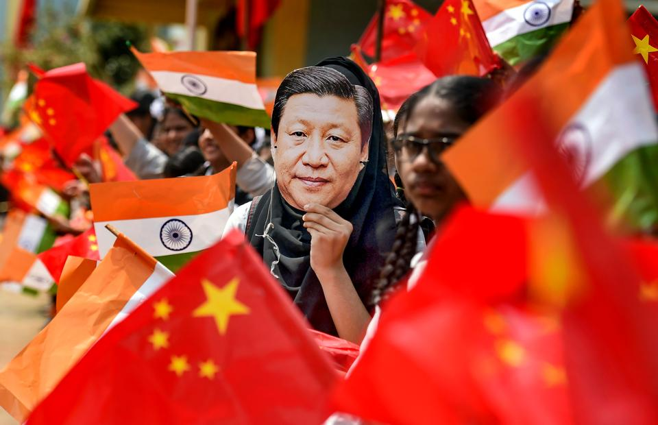 School students wave the national flag of China and India ahead of Chinese President Xi Jinping's visit Chennai