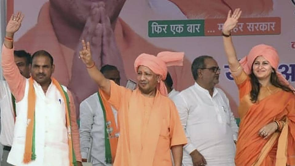 Uttar Pradesh Chief Minister Yogi Adityanath waves at his supporters during a campaign ahead of Haryana Assembly polls, at Adampur, in Hisar district of Haryana, Saturday, Oct. 12, 2019.