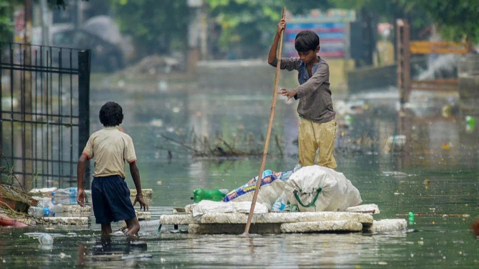 A rag picker rows a makeshift boat as he collects plastic bottles floating on floodwaters at Rajendra Nagar area, in Patna, Bihar. (PTI)