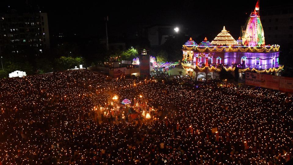 "Thousands of devotees hold lamps to during ""Maha Arti"" for Goddess Umiya on Durgashtmi, at Umiyadham Temple, in Surat, Gujarat. (PTI)"