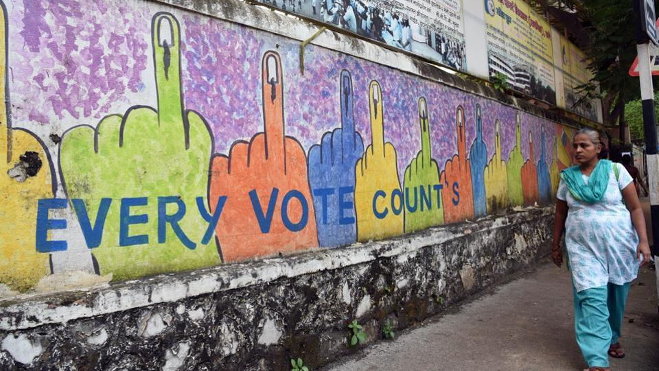 A woman passes by a wall mural that urges citizens to cast their vote ahead of the Maharashtra state assembly elections, near Masunda Lake, in Thane, Maharashtra. (Praful Gangurde / HT Photo)