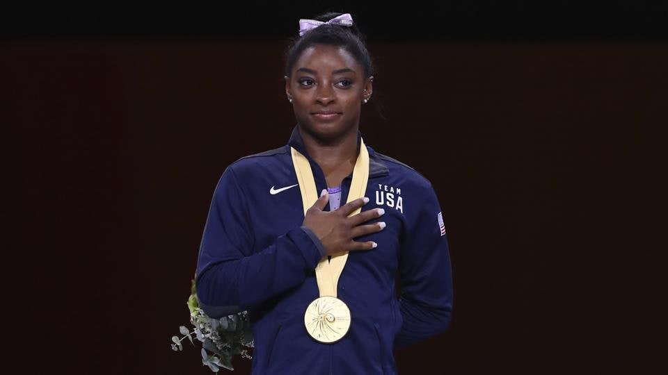 Simone Biles listens to the national anthem during the award ceremony at the Gymnastics World Championships in Stuttgart.