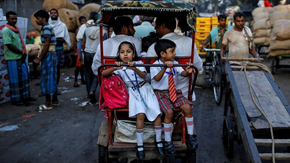 School children ride in a cycle rickshaw through a market in the old quarters of Delhi. (Danish Siddiqui / REUTERS)