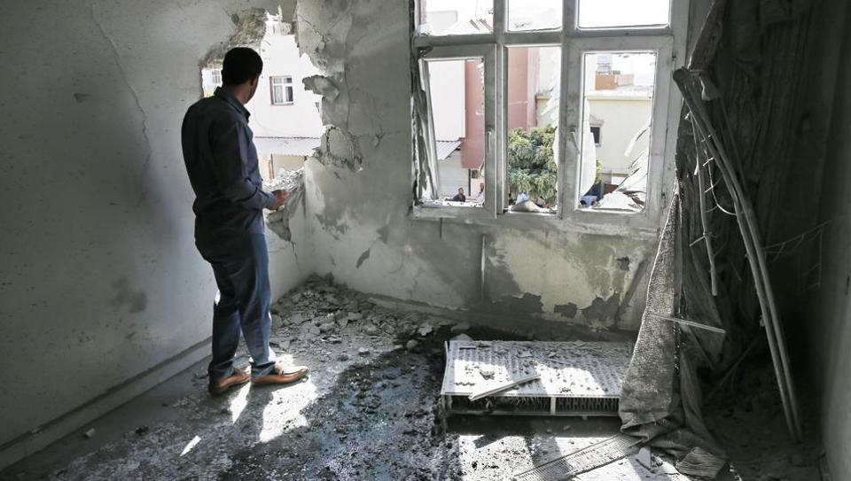 A person inspects the damage on a building hit by a mortar fired from inside Syria, in Akcakale, Sanliurfa province, southeastern Turkey, Sunday, Oct. 13, 2019.