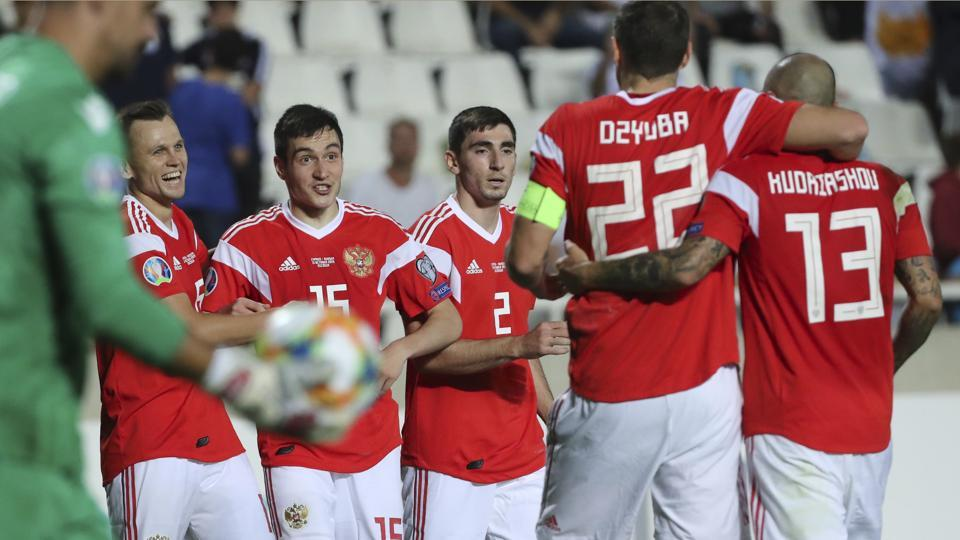 Russia's Denis Cheryshev, second left, celebrates with teammates after scoring his side's fifth goal during the Euro 2020